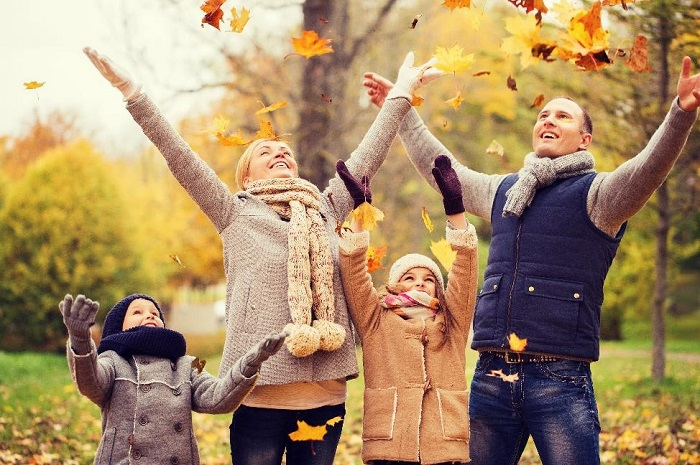 family of four wearing fall clothing throwing leaves into the air