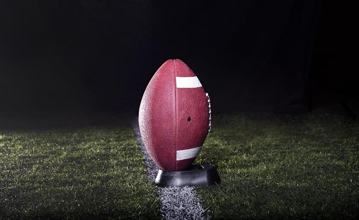 football resting in its stand on a grass football field with a black background