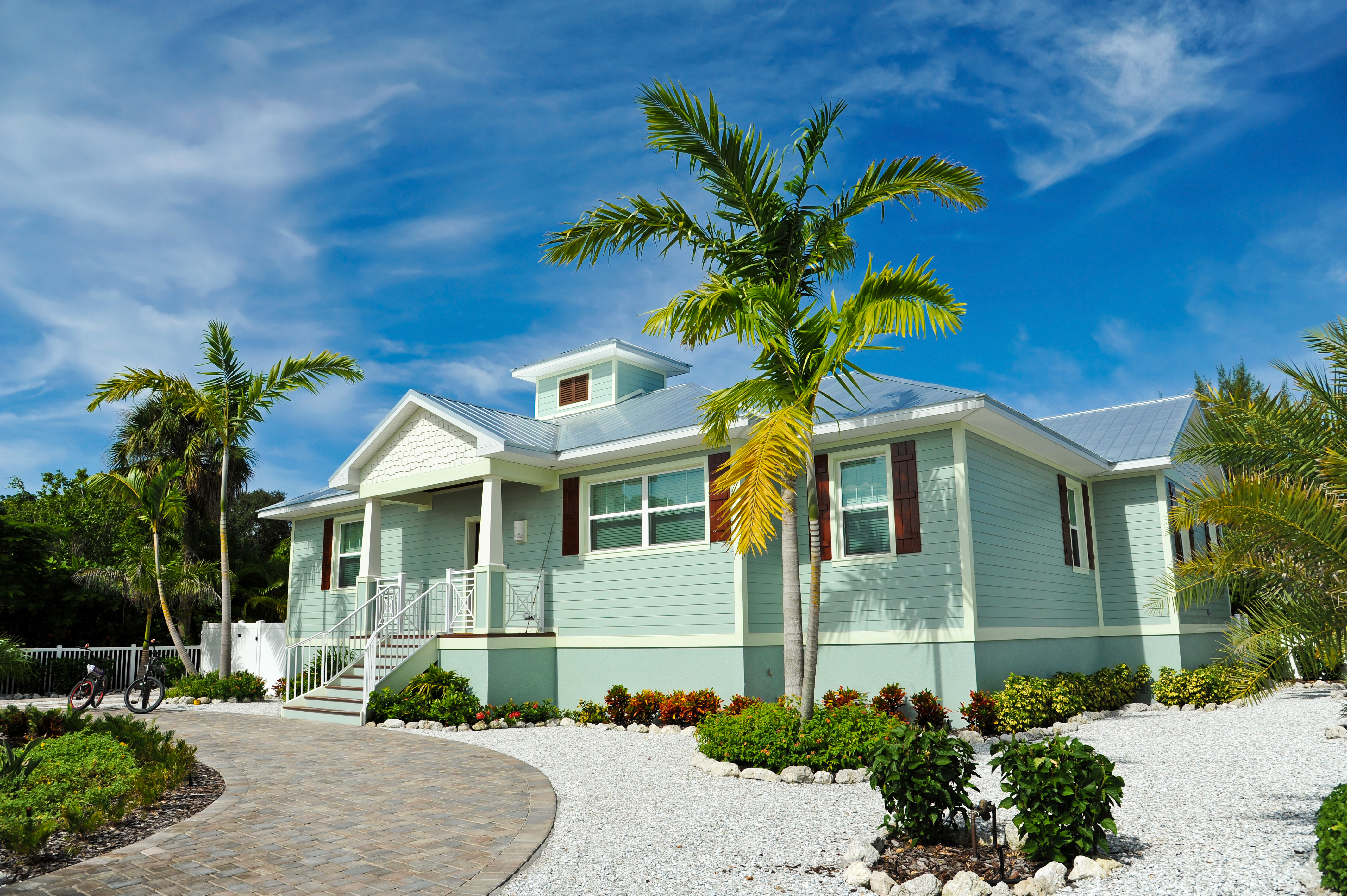 front view of a sea green beachhouse with palm trees and pebbles lining the stone driveway