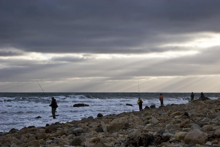 A man casts a fishing line off of a rocky northeastern beach under cloudy skies.