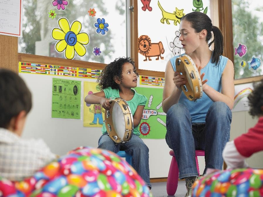 A woman leads a group of small children in a song and playing small musical instruments like tambourines.