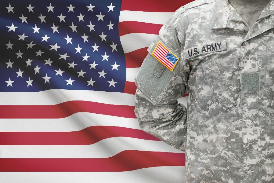 military man standing in front of american flag