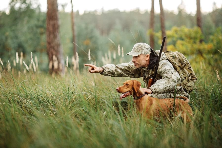 Man in hunter's camouflage points while crouched next to his dog