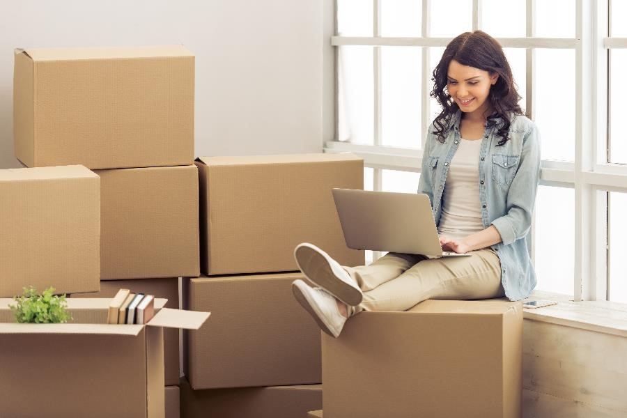 Young woman sitting on a pile of cardboard boxes after moving into her new dorm room.